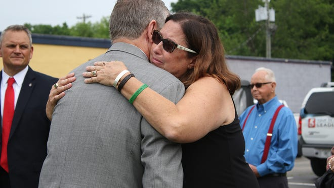 Tyler Head's mother Gina Head-Heiber hugs State Rep. Joe Pitts at the unveiling of Head's memorial sign on Madison Street on Friday. The Tyler Head Law allows innocent victims killed in impaired driver accidents be memorialized by street signs. The law goes into effect July 1.