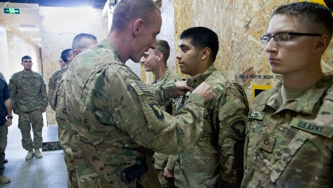 Maj. Gen. Gary Volesky, commander of the Combined Joint Forces Land Command - Operation Inherent Resolve, pins a Combat Action Badge on Pfc. Marvin Acevedo of Troop A, 1st Squadron, 75th Calvary Regiment, Task Force Strike, and five other soldiers on June 2 in Mahkmour, Iraq.  The soldiers received Combat Action Badges for taking hostile indirect fire in Mahkmour on May 2.