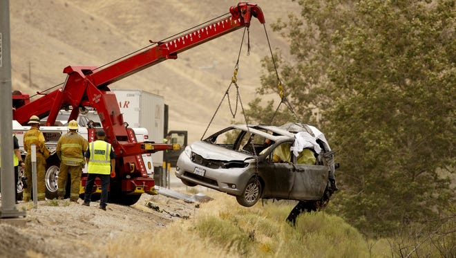 A heavy tow truck lifts a vehicle to the side of the 5 freeway as investigators look over the scene of an accident on Tuesday, June 28, 2016 in Gorman, Calif.  A minivan got in a minor collision and stopped on the shoulder. It was still partially in a lane when a semitrailer hit it and it burst into flames with two women and children inside, California Highway Patrol Officer Monica Posada said.  (Al Seib/Los Angeles Times via AP)  NO FORNS; NO SALES; MAGS OUT; ORANGE COUNTY REGISTER OUT; LOS ANGELES DAILY NEWS OUT; INLAND VALLEY DAILY BULLETIN OUT; MANDATORY CREDIT, TV OUT