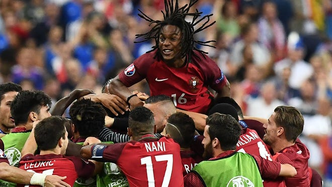 Portugal's midfielder Renato Sanches celebrates with teammates after Portugal beat their hosts France 1-0 in the Euro 2016 final football match between France and Portugal.