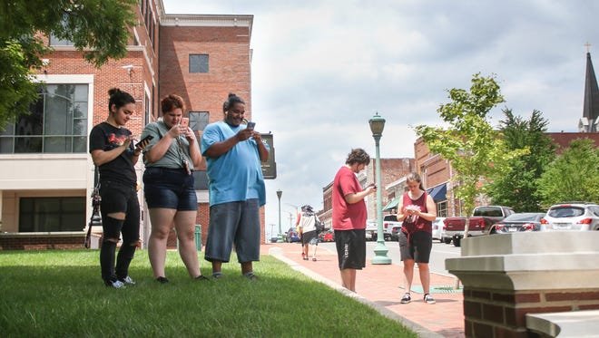 Groups surround the Montgomery County Courthouse in search of Pokemon in the new Pokemon Go app. The courthouse hosts several Pokestops, where players can pick up items necessary to the game.
