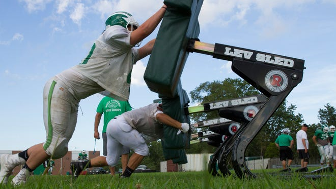 Lineman work the sleds during Brick High School football practice in Brick, NJ on August 18, 2016.