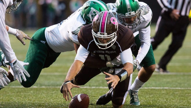Western Michigan quarterback Zach Terrell (11) attempts to recover a fumble as he is tackled by Eastern Michigan players during an NCAA college football game in Kalamazoo.