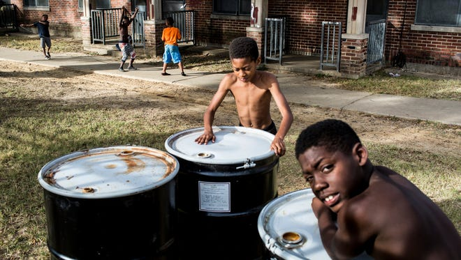 Maxwell Lee, 11, center, and Ashton Dotson, 9, right, lean on barrels near an observation monitoring well while taking a break from playing jump rope with their friends in Foote Homes on Oct. 10, 2016.