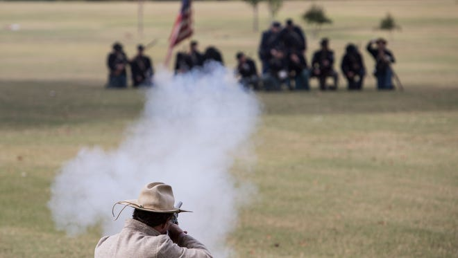 A Confederate soldier reenactor fires towards Union troops during the Battle of Bartlett Civil War battle re-enactment at Freeman Park in Bartlett Saturday.
