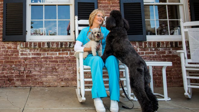Dr. Kathy Kunkel plays with Polo and Lola in front of Little House Animal hospital in Franklin, Tenn. Through numerous community actions Little House Animal Hospital has an all-around commitment to saving, healing and caring for animals.