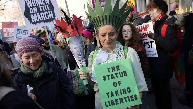 FILE- In this Jan. 21, 2017, file photo, demonstrators take part in the Women's March in London the day after the inauguration of U.S. President Donald Trump. Signs from the women's marches around the world are being saved as cultural treasures by museums, libraries and colleges. (AP Photo/Tim Ireland, File)