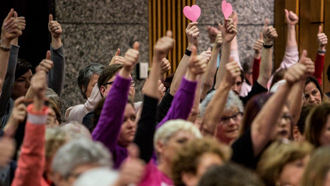 Supporters of Planned Parenthood raise their thumbs to show support while Planned Parenthood CEO Ashley Coffield speaks during the Shelby County Commissioners meeting where a resolution to approve a service provider contract with Planned Parenthood Greater Memphis Region was being discussed.