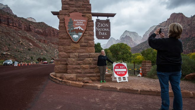 Ellen Smiley takes a photo of her sister, Dana Deardorff outside Zion National Park on Thursday, October 10, 2013.