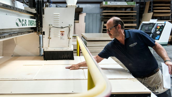 David Sidenbender inspects the cuts the CNC router machine makes into plywood that will be used to assemble cabinets inside the milling room at the Fehrenbacher Cabinets facility in Evansville, Ind., on Friday, June 16, 2017. After being computer programed, the CNC Router machine uses 12 different tools to cut and drill pieces of wood.