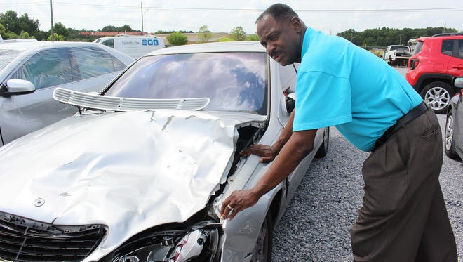 Montgomery Councilman David Burkette inspects damage to his car when it was struck by a cow recently. Alvin Benn/Special to the Advertiser