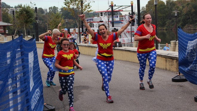Dee Cook had reason to jump for joy as she and her friends crossed the finish line at Saturday's Super Hero 5K race to benefit Child Protect in Montgomery. Alvin Benn/Special to the Advertiser.