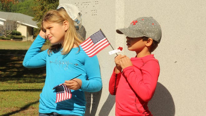 Leila Moore, 8, and her brother, Hayes Moore, 7, hold American flags at a Selma monument honoring Dallas County residents killed during the Korean War. Alvin Benn/Special to the Advertiser
