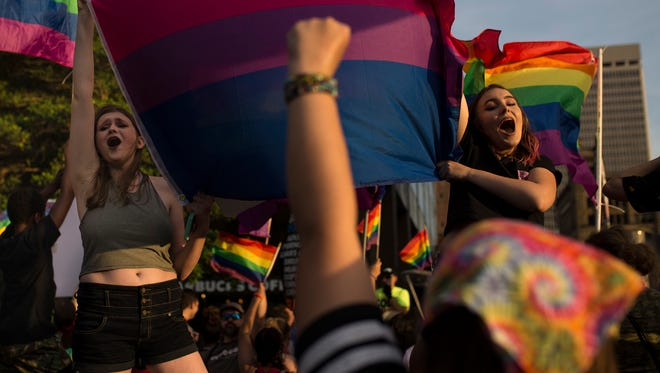 Laura Cambden, left, and Abbie Puckett wave a rainbow flag and cheer on participants during the Kentuckiana Pride Festival Parade on Main Street. June 16, 2017