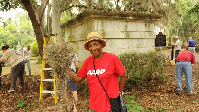 Evelyn Cox holds a handful of moss taken from trees in Selma during a clean-up effort at Old Live Oak Cemetery on Saturday. Alvin Benn/Special to the Advertiser.