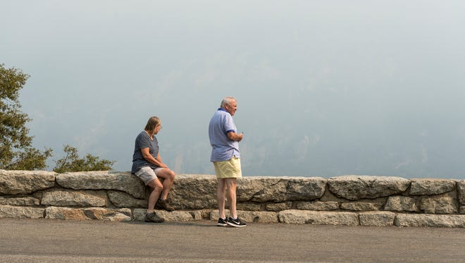 Dee Parry, left, and Haydn Parry of London strain to see vistas obscured by smoke from the Ferguson Fire near Tunnel View in Yosemite National Park on Tuesday, July 24, 2018. It was the couple's first visit to the park.
