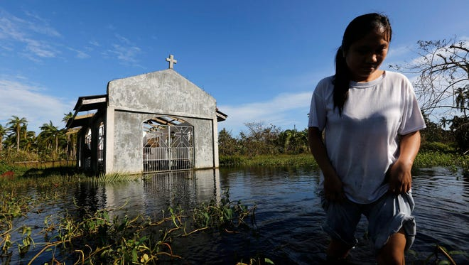 A Filipino woman wades through floodwater next to a damaged church at Dolores, Samar Island, in the Philippines on Monday. Typhoon Hagupit moved toward the capital Manila after striking eastern and central regions of the country.