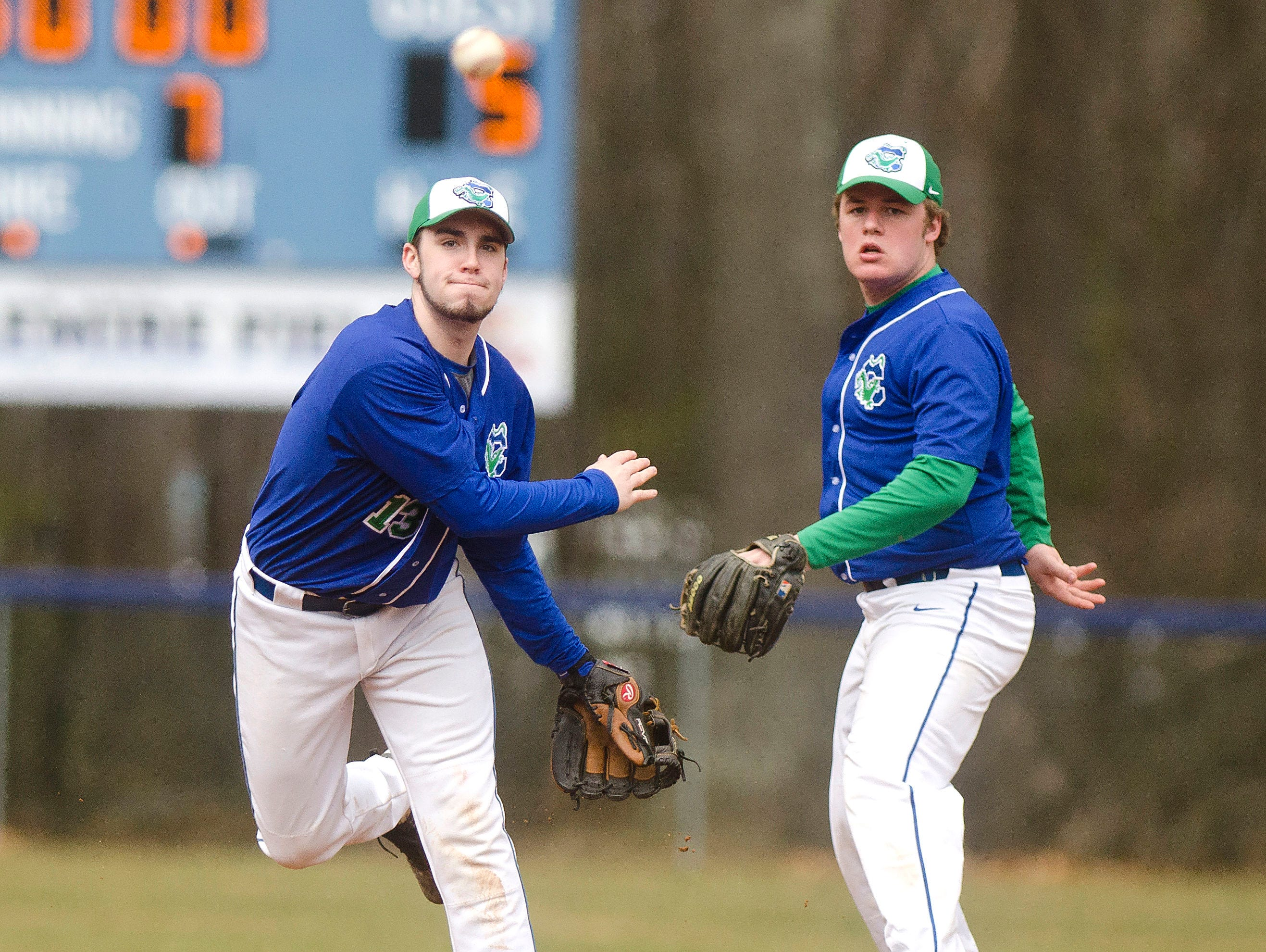 Colchester shortstop Derek Sanderson, left, throws a runner out at first to complete a double play started by Jared Antoniak, right, during last year's game against Mount Abraham.