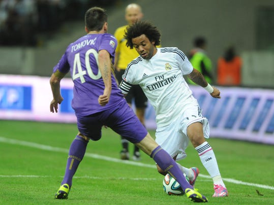 Real Madrid's Marcelo from Brazil, right, challenge for the ball with Fiorentina's Nenad Tomovic from Serbia during their friendly soccer match in Warsaw, Poland, Saturday, Aug. 16, 2014. ( AP Photo/Alik Keplicz)