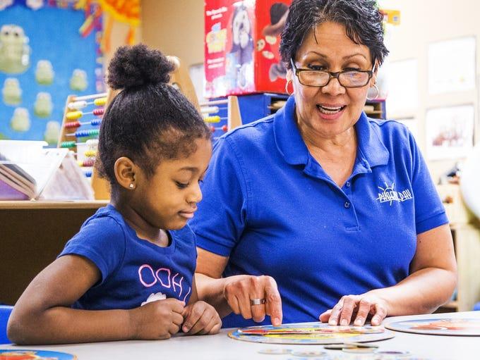 Teacher Rosa Bravo works with 4-year-old Yashimebet