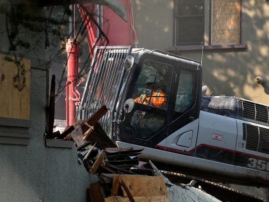 Crews work Monday on the demolition of the Dobrowsky