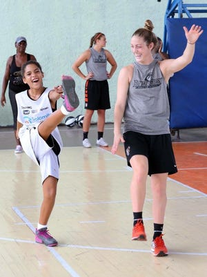 Bellevue graduate Carly Santoro, right, made a friend as members of Bowling Green State University's women's basketball team instructed children at a clinic in Cuba. Santoro is a freshman for the Falcons and Andrea Cecil, center, is a freshman.