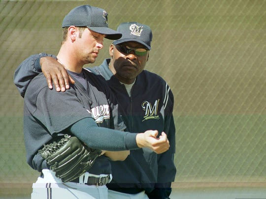 J.M. Gold, playing in the Milwaukee Brewers' organization in 2002, looks at his right arm along with pitching coach  Dave Stewart .