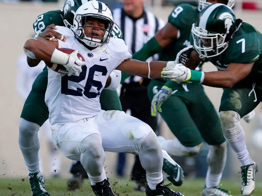 Penn State running back Saquon Barkley, center, is stopped by Michigan State's Shilique Calhoun, left, and Demetrious Cox, right, during the second quarter of an NCAA college football game, Saturday, Nov. 28, 2015, in East Lansing, Mich. Michigan State won 55-16.