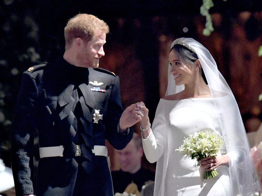 Meghan Markle and Prince Harry hold hands on the steps
