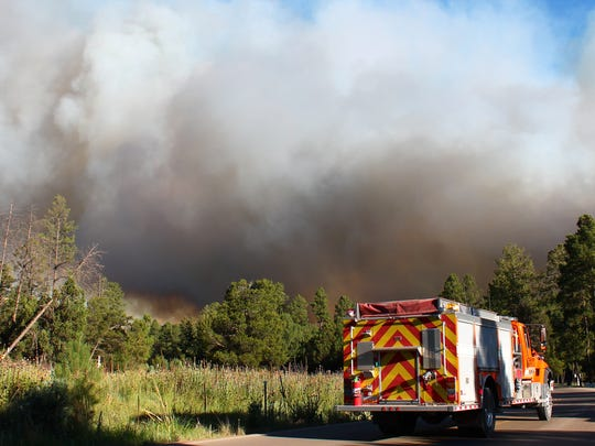 A fire truck stands by as the blaze burns in Timberon on Wednesday.