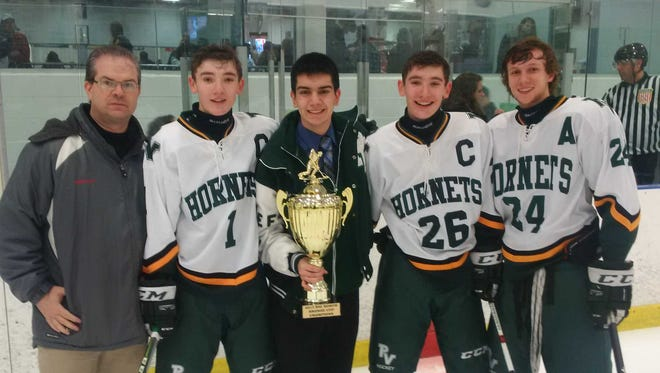 Big North tournament director Cory Robinson presents the Big North Bronze Cup to the Passaic Valley/Cedar Grove hockey captains (from left), Nick LoPresti, Jack Prospero, Alex LoPresti and Vincent DiNardo on Friday night at Ice Vault.