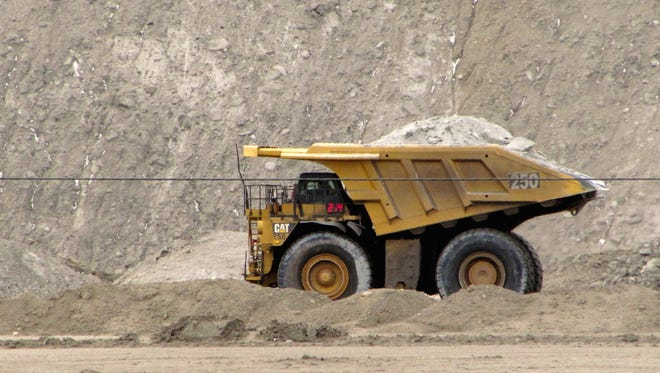 In this March 26, 2013 file photo, a house-sized dump truck hauls dirt and rock at the Black Thunder coal mine in northeast Wyoming's Powder River Basin near Wright, Wyo.
