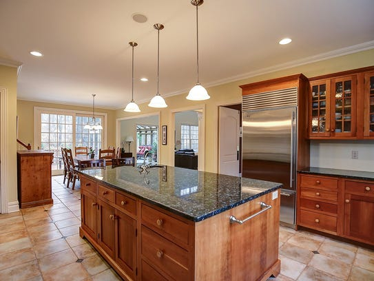 The kitchen has stone tile floors, a large center island
