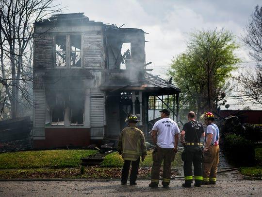 Memphis firefighters watch a 2 1/2 story house smolder