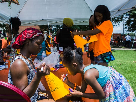 Ebony Howell, 19, watches her niece, Zaylynn Anderson, 6, design a hat during the Wear Orange Block Party at Howze Park on June 2, 2018. The event was hosted by the Memphis chapter of Moms Demand Action for Gun Sense in America.