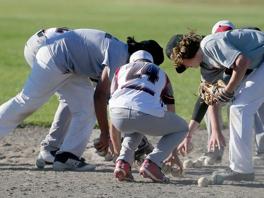 Renegades players collect baseball at second base during practice at Marcus Whitman Junior High School in Port Orchard.