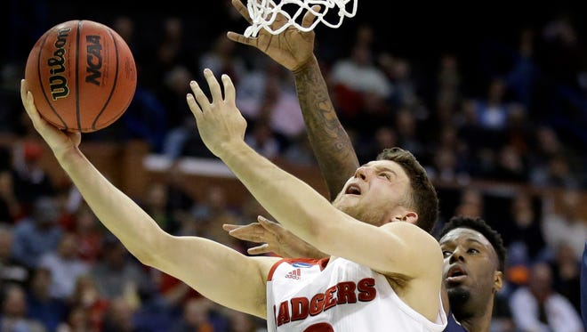 Wisconsin's Zak Showalter, left, heads to the basket as Pittsburgh's Jamel Artis defends during the first half of a first-round men's college basketball game in the NCAA tournament on Friday in St. Louis.