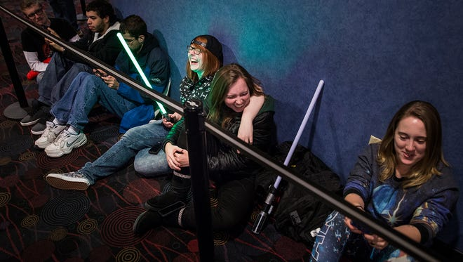 Star Wars fans play with lightsabers while waiting in line for the premiere of Episode VII at AMC Showplace Muncie 12.