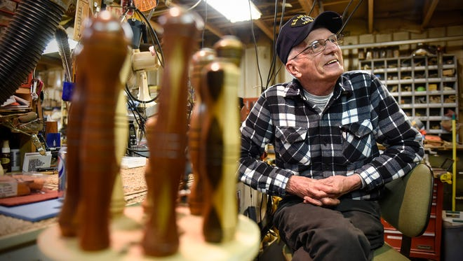 Ray Tuholsky smiles while talking about his work Wednesday, April 19, in his workshop near St. Anna. Tuholsky creates hundreds of comfort crosses and fishing lure kits each year.