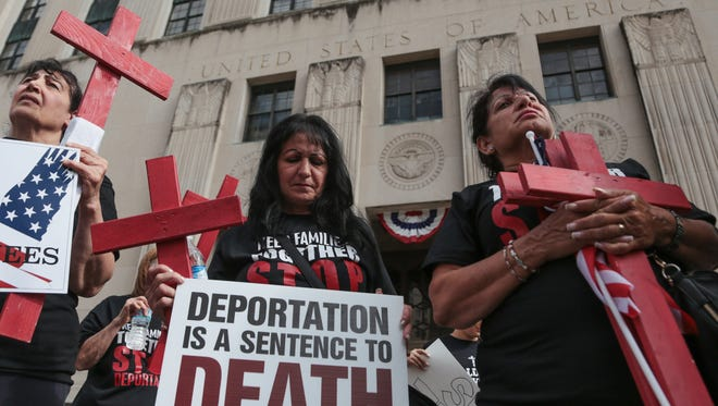 Ikval Marogi, right, of Warren and Elham Mona, center, of Sterling Heights listen to a speaker as families of Iraqi immigrants from metro Detroit who were detained by ICE gather outside of the federal courthouse in downtown Detroit on Thursday August 31, 2017.