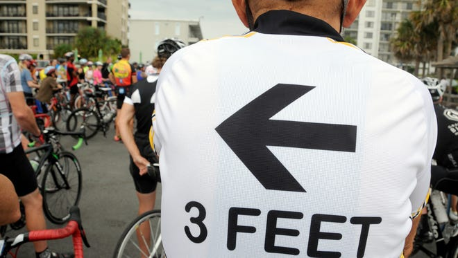 A man in Myrtle Beach, S.C., wears a T-shirt warning car passengers to stay 3 feet away as bicyclists riding all types of bikes gathered Sept. 21, 2013, in the oceanside town.