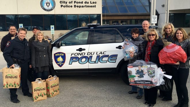 Members of the Fond du Lac Police Department and police chaplains provide gifts and food to 72 local families in need.