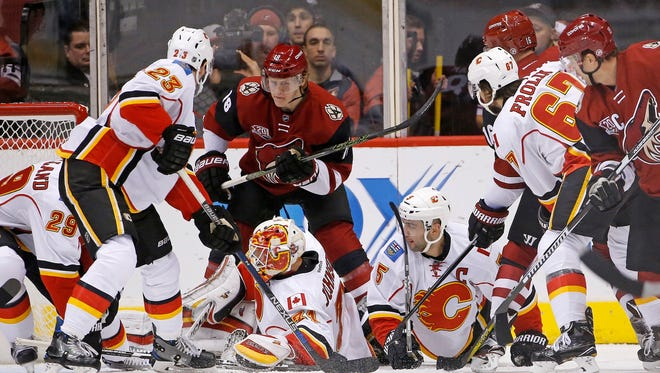 Arizona Coyotes left wing Max Domi (16) gets the puck past Calgary Flames goalie Chad Johnson, bottom left, for a goal as Flames' defenseman Deryk Engelland (29), center Sean Monahan (23), defenseman Mark Giordano (5), right wing Michael Frolik (67), and Coyotes' center Christian Dvorak (18) and right wing Shane Doan, right, all look for the puck during the first period of an NHL hockey game Thursday, Dec. 8, 2016, in Glendale, Ariz.
