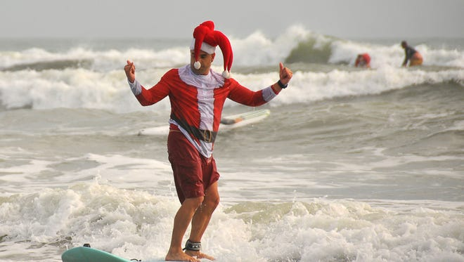 Cocoa Beach City commissioner Ed Martinez was one of hundreds of Surfing Santas to catch a wave on Christmas Eve 2016 during the annual Surfing Santas event.