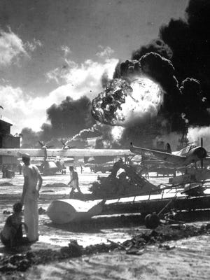 Sailors among wrecked airplanes watch the Japanese attack on Pearl Harbor, Hawaii, on Dec. 7, 1941.