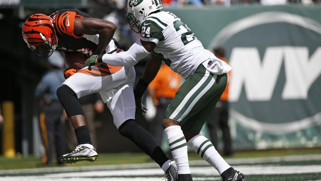 Cincinnati Bengals wide receiver A.J. Green scores a touchdown as the Jets' Darrelle Revis attempts to tackle him during the first half of their game Sunday at MetLife Stadium in East Rutherford.