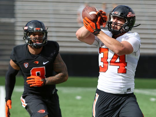 Oregon State Ryan Nall (34) makes a catch as Rommel Mageo looks on  during the first day of fall practice on Saturday, Aug. 8, 2015, in Corvallis, Ore.