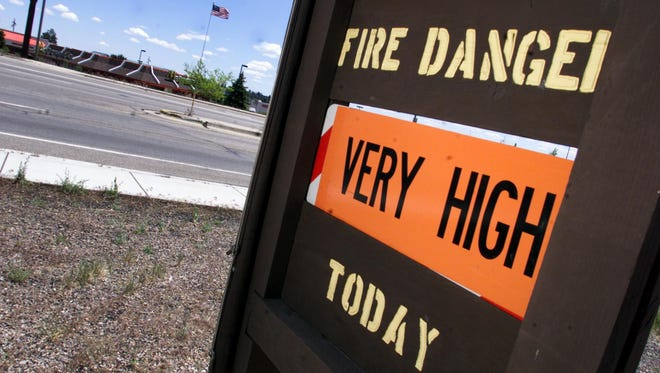 A sign in East Flagstaff reminds residents of the fire danger as high winds blow a flag in the background.
