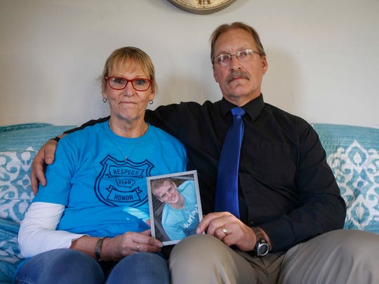 Randy and Jayne Martin hold a photo of their son, Justin, at their home on Tuesday, Oct. 24, 2017 in Rockwell City. Justin Martin, a police officer at the Urbandale Police Department, was one of two officers gunned down in an ambush by Scott Michael Greene last year.
