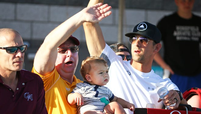 Arizona State swimming coach Bob Bowman holds Boomer Phelps, the son of Michael Phelps as they cheer on Chase Kalisz to victory in the Men 400 Meter Individual Medley final during the Arena Pro Swim Series Mesa on Friday, April 14, 2017 at Skyline Aquatic Center in Mesa.